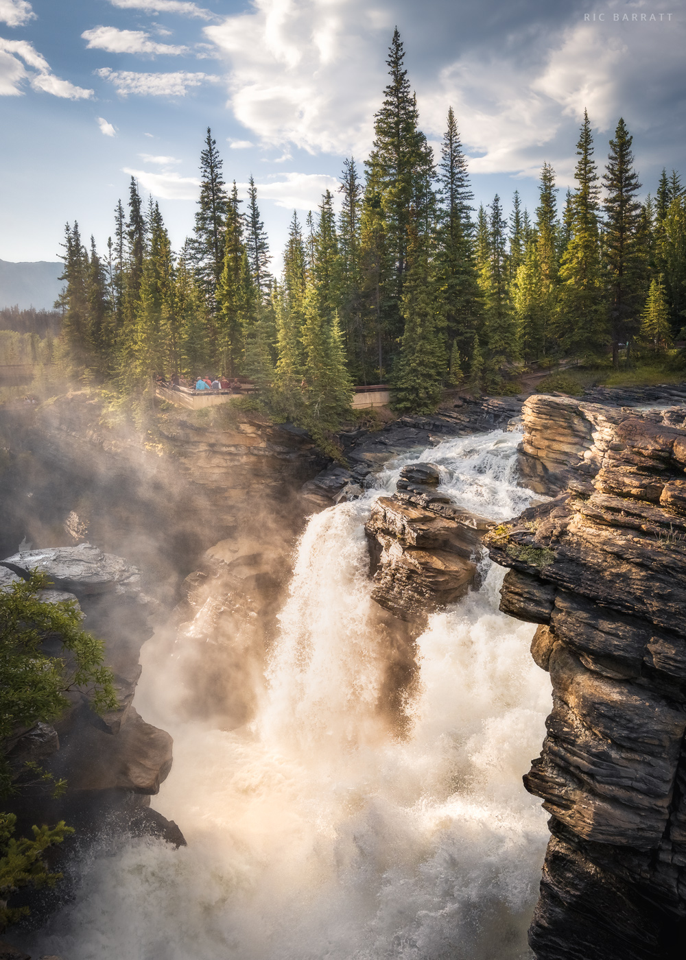 Thunderous waterfall cascading over a cliff in Canadian forest land.