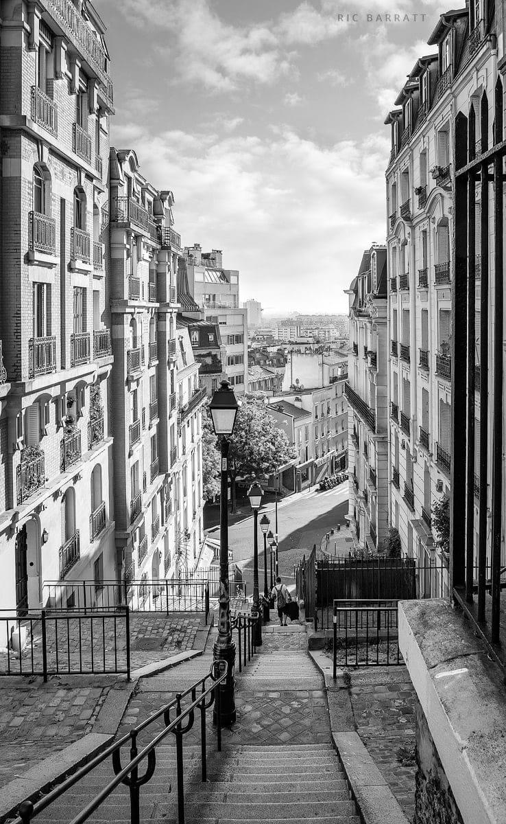 Long stairway leading down between tall Parisian buildings.