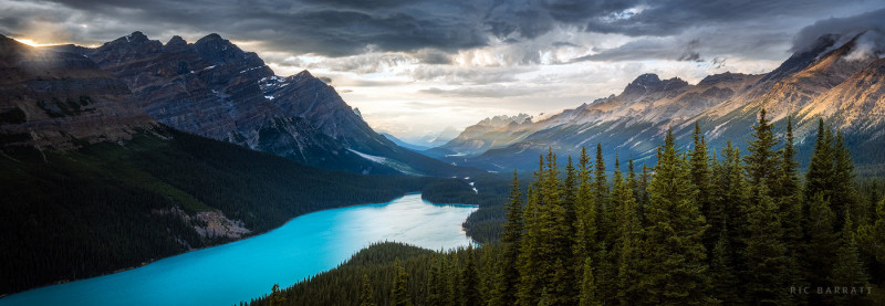 Large turquoise lake sits at the bottom of forested valley surrounded by majestic mountains lit by evening sun.