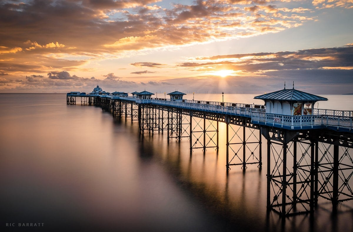 Long white and blue pier travels out into the sea under a brilliant orange sunrise.