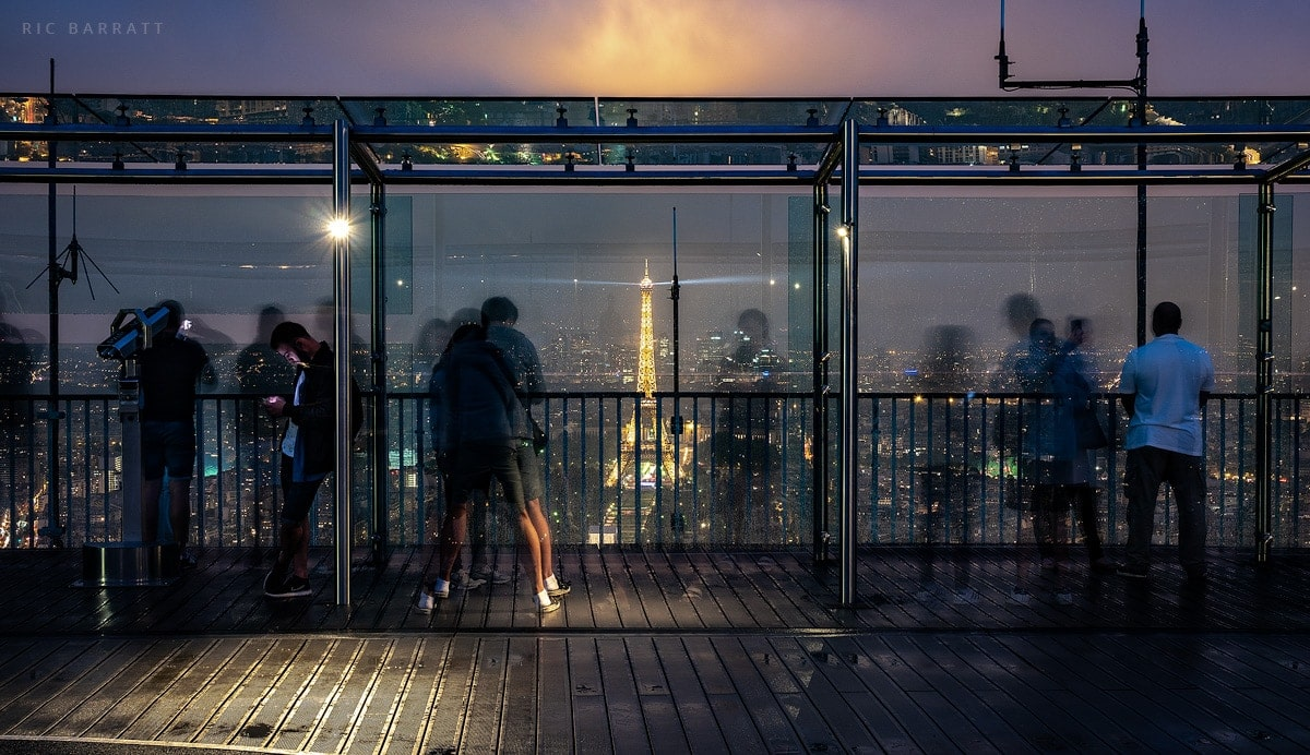 Tourists look out from a high viewing platform in Paris at night. Illuminated Eiffel Tower in the distance.