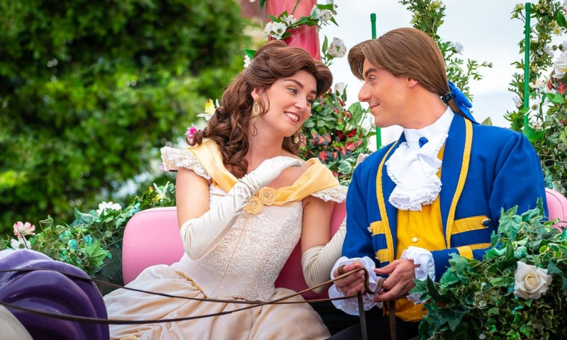 Disney prince and princess gaze at each other longingly in a horse-drawn carriage.