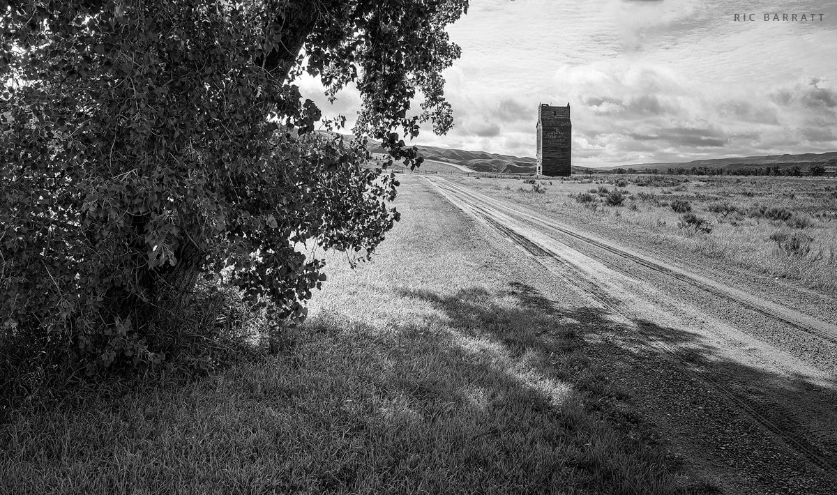 Gravel road leads towards dilapidated old grain elevator.
