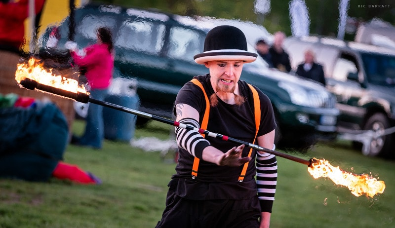 Circus performer performs tricks with flaming baton.