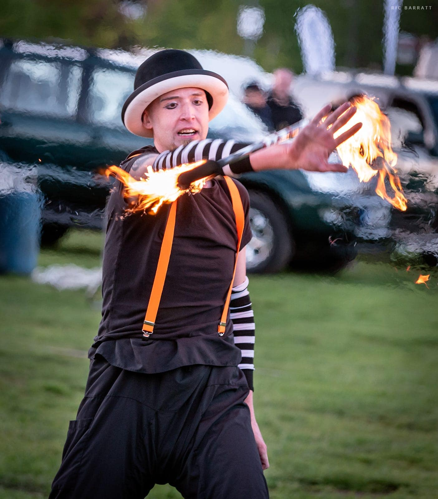 Circus perform twirls a flaming baton around his arm.