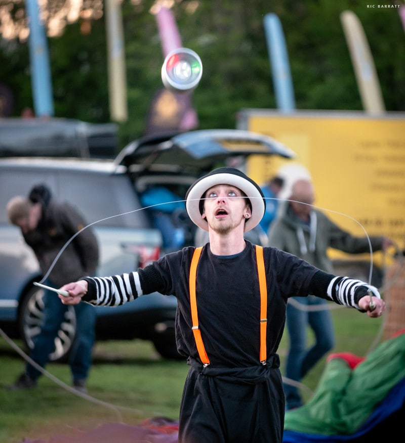 Circus artist dressed in black and white performs offstring yoyo tricks.
