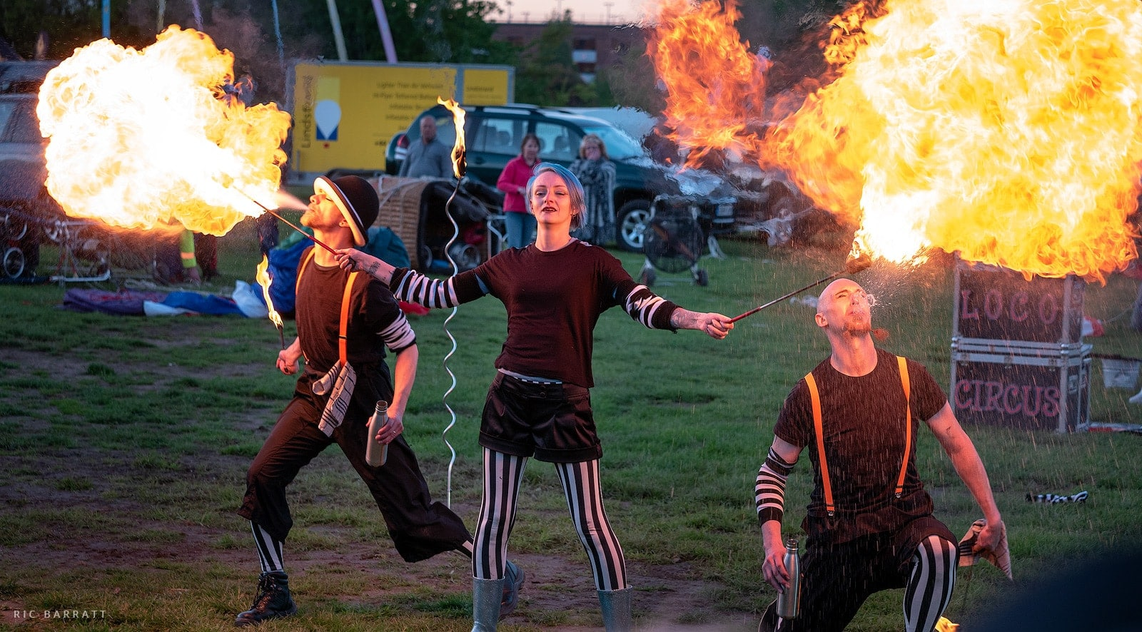Female helps ignite the spray from two male fire breathers.