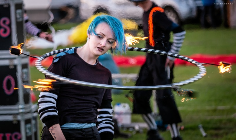 Female performer full of concentraion spins flaming hula-hoop around her shoulders.