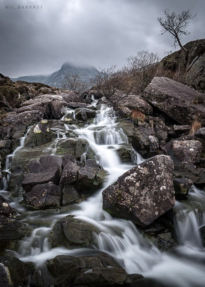 Small waterfall stream cascades down grey rocks in overcast mountainous terrain.