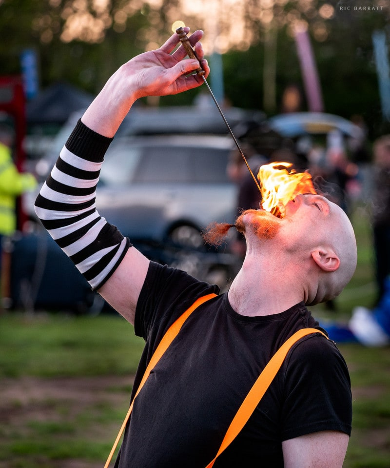 Male circus perform extinguishes fire in his mouth.