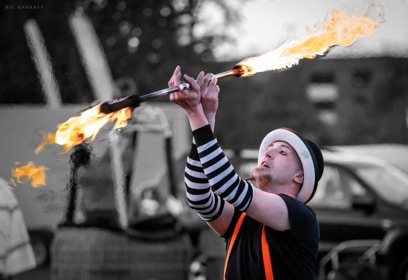 Male circus performer twirls flaming baton above his head.