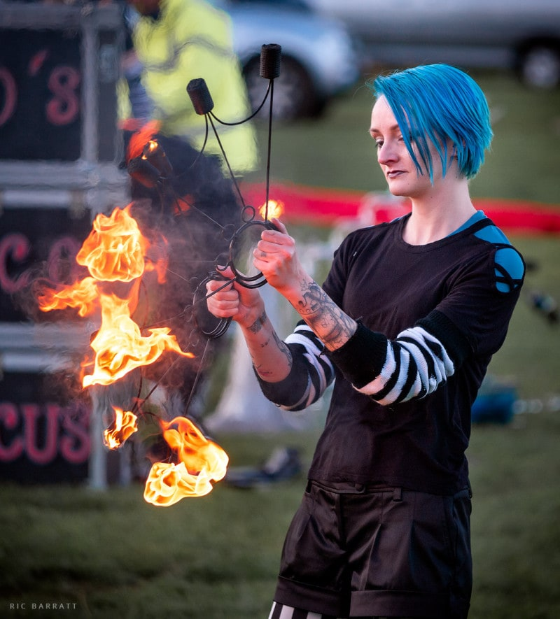 Female circus artist ignites apparatus on fire ready for performance.