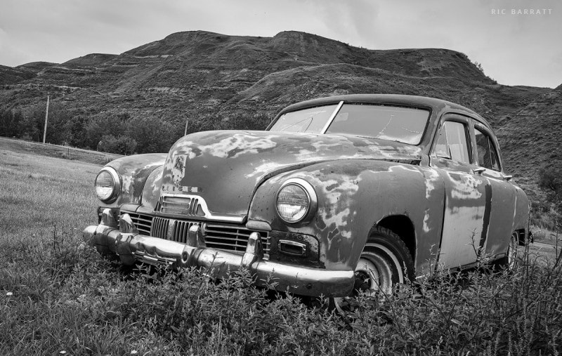 Rusty old car sits abandoned in front of canyon hills.