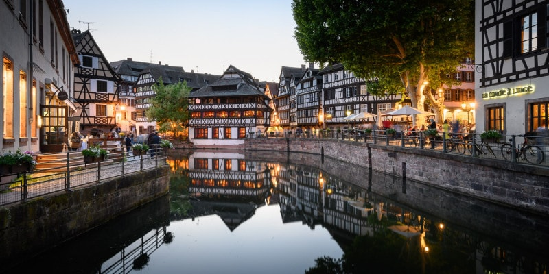 Quaint timber frame buildings surround a river in Petite France. Early evening.