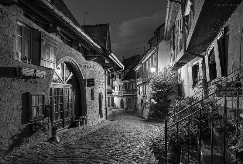 Night shot of empty, narrow cobbled street and old timber buildings.