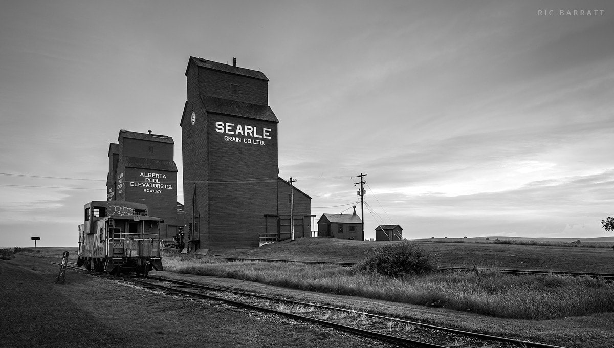 Imposing grain elevators and disused, graffiti rail car.