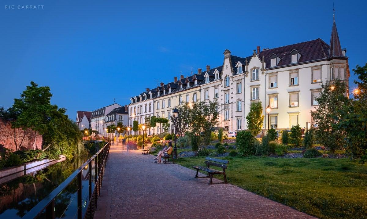 Urban riverside footpath at dusk in Colmar, France.