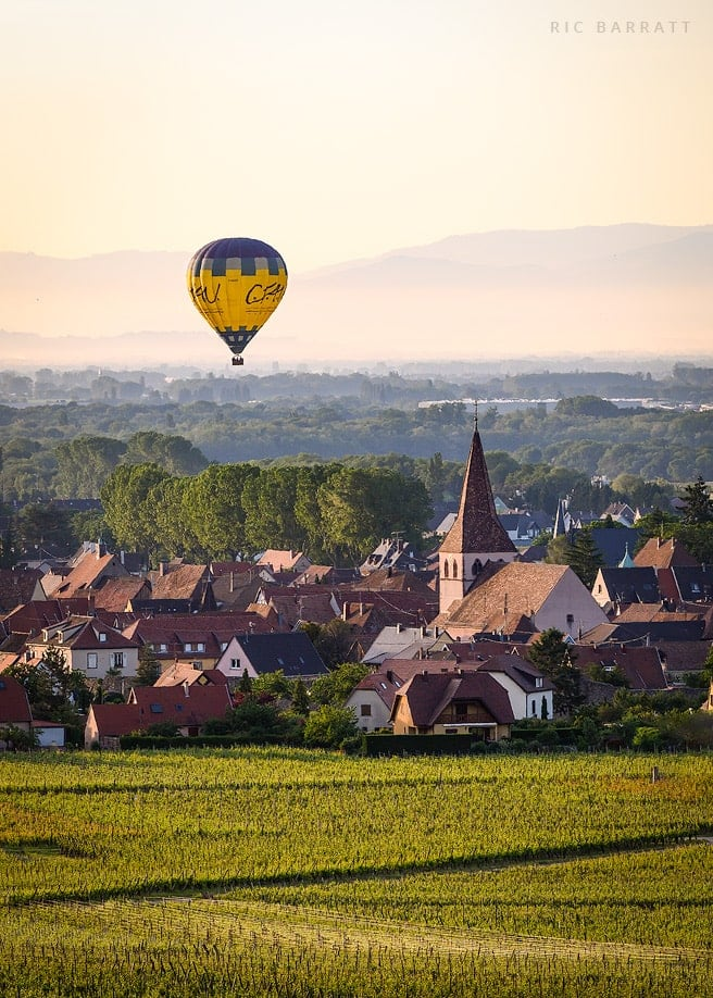 Yellow and blue hot air balloon floats above French village.