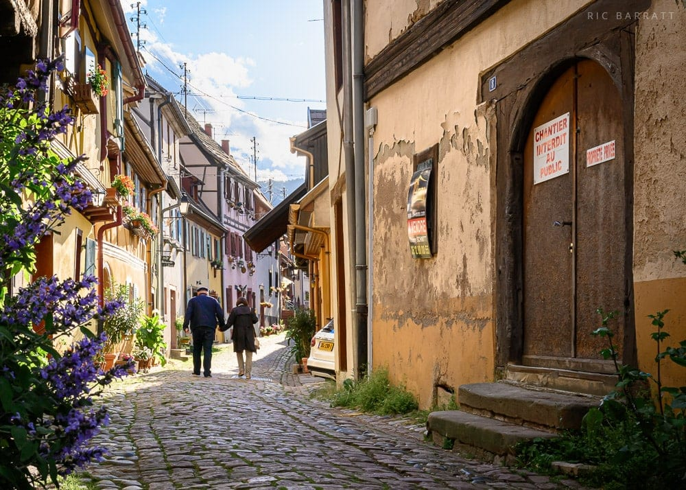Elderly couple holding hands as they walk down cobbled street with brightly coloured terraced cottages.