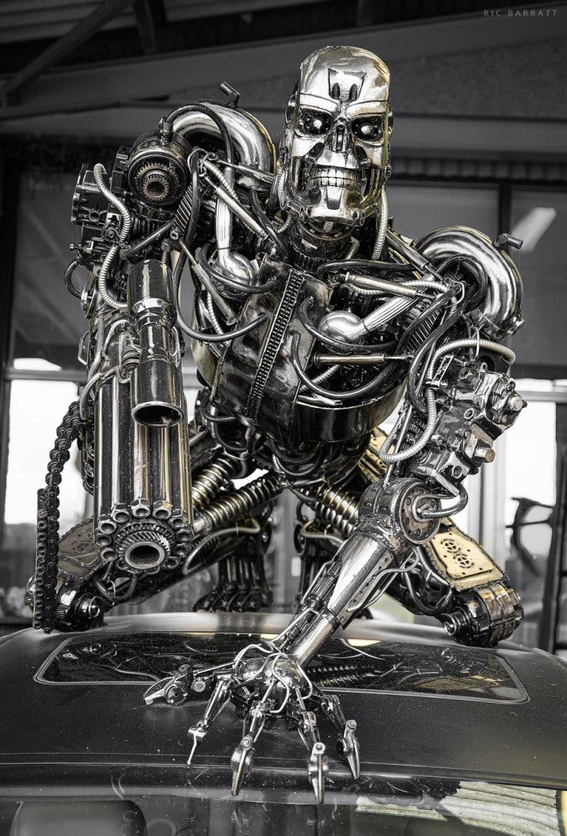 Crouching metal sculpture of Terminator robot made from scrap metal alloy elements.