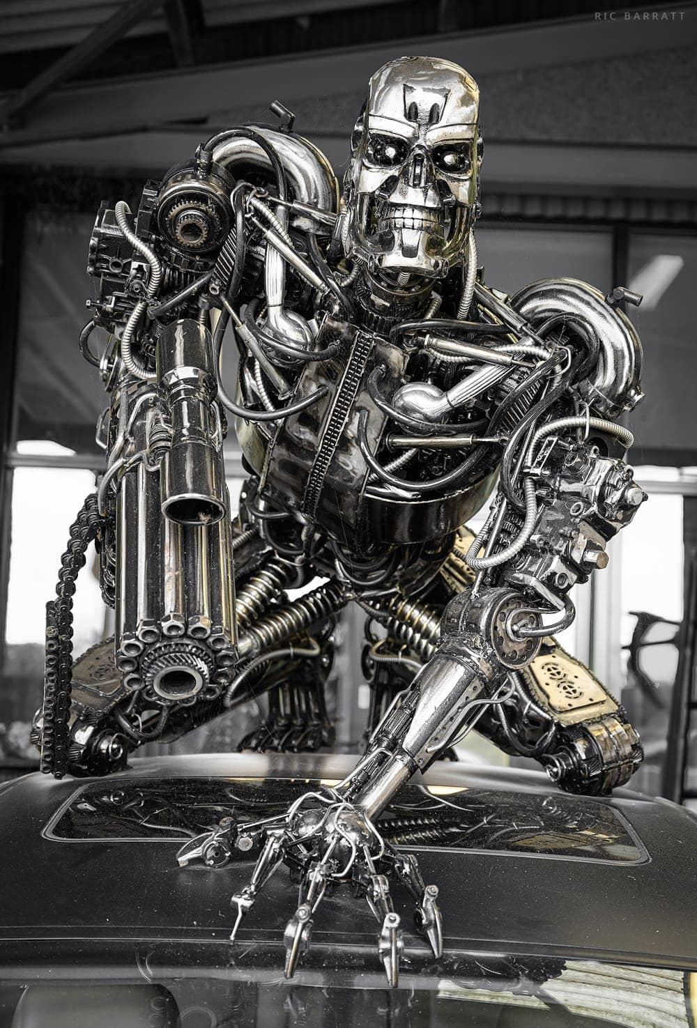 Crouching metal sculpture of Terminator robot made from scrap metal alloy elements.
