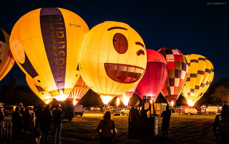 Nine tethered balloons of various designs illuminated with fire from their baskets underneath.
