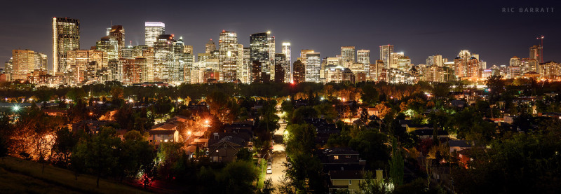 Dazzling skyscrapers of downtown Calgary reaching into dark night sky.