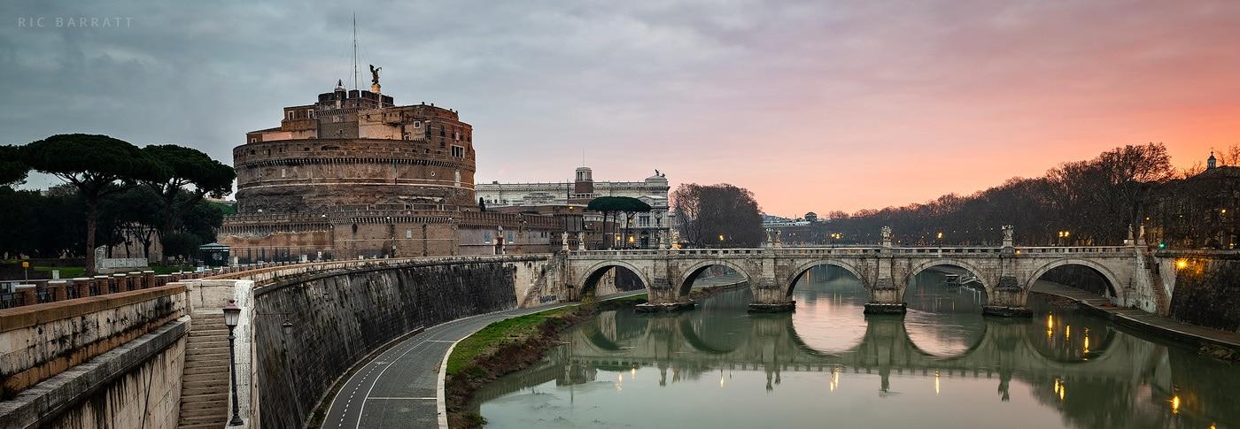 Circular, brown castle and grey bridge crossing calm turquoise river.