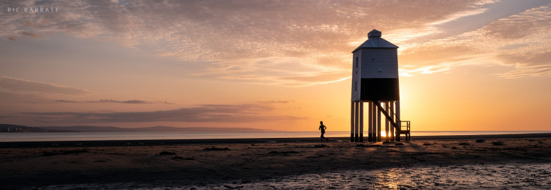 Runner runs past a stilted, wooden lighthouse at sunset.