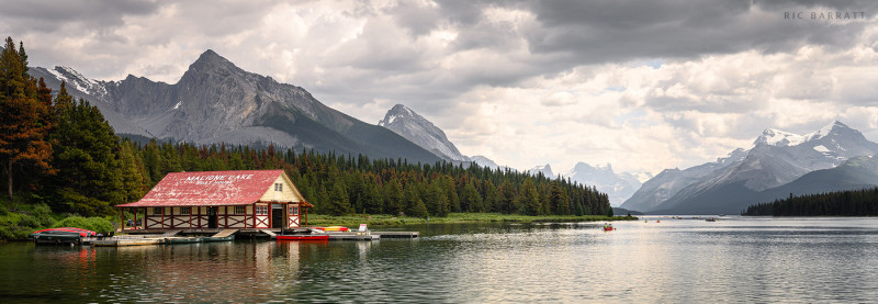 Red-roofed timber boat house on the edge of vast and mountainous Maligne Lake in the Canadian Rockies.