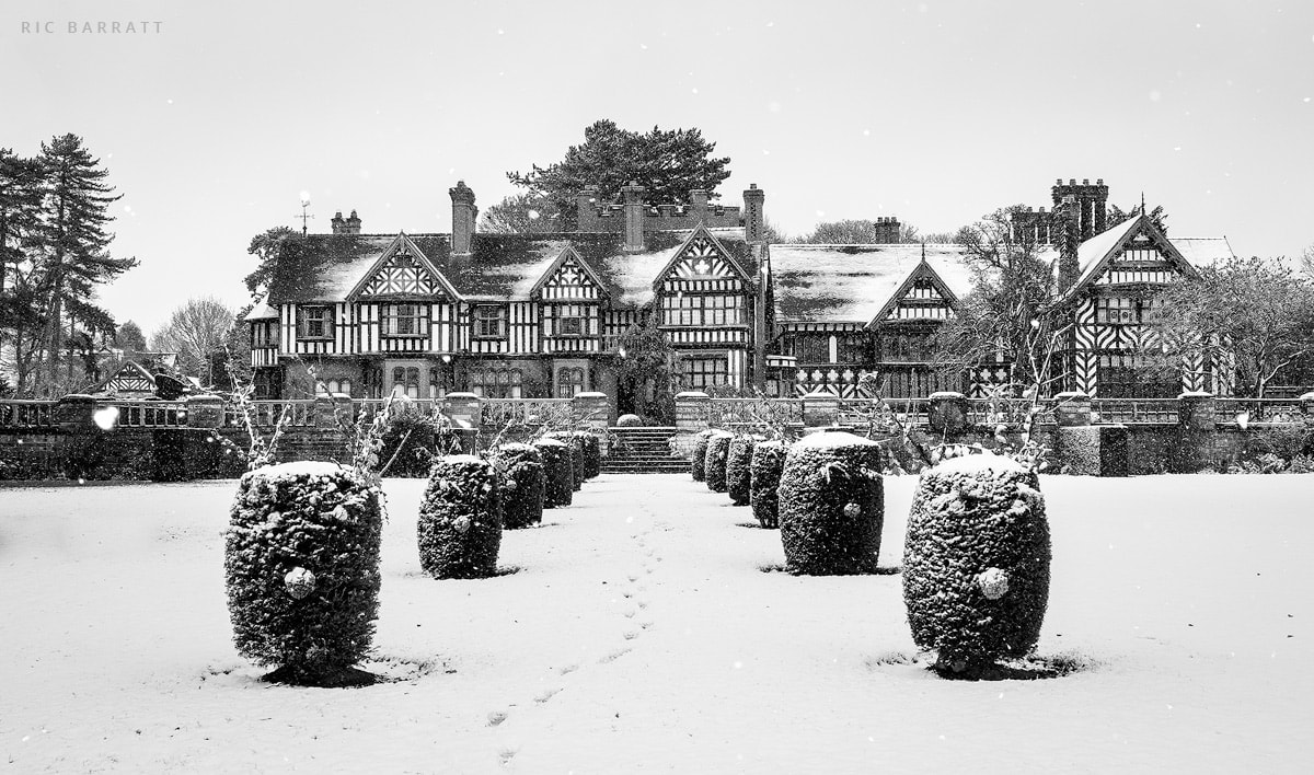 Old timber and brick country manor and surrounding gardens covered by snow.