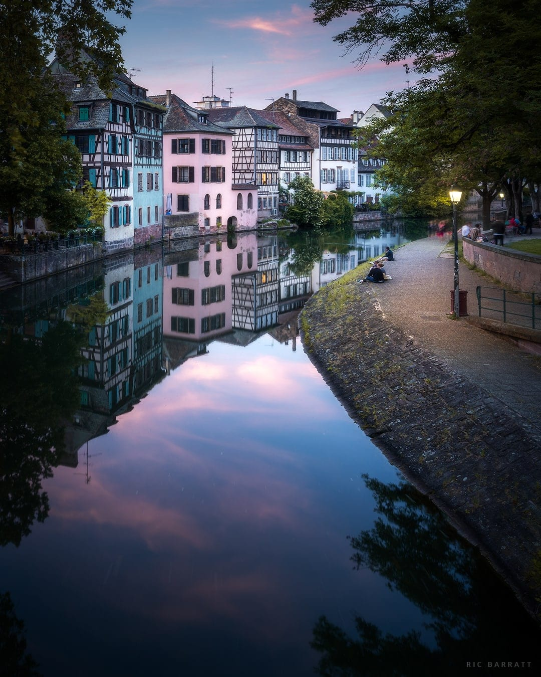 A clam, peaceful river leads its way past the half-timbered houses at dusk.