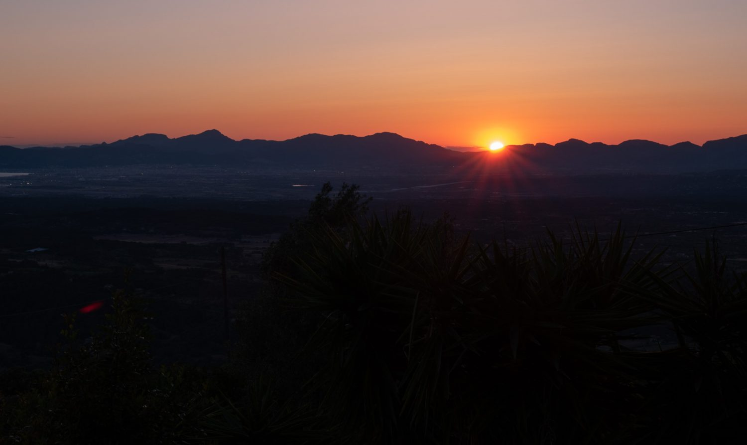 Shot of an orange sunset with foreground in complete darkness.
